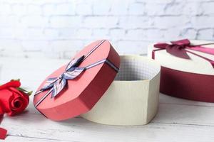 scatola regalo a forma di cuore e rosa rossa sul tavolo foto