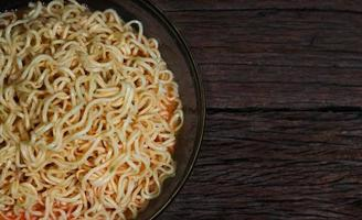 spaghetti istantanei in una ciotola su fondo in legno foto