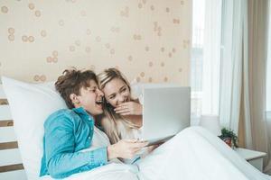 coppia felice utilizzando il computer portatile sul letto