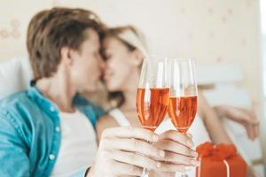 coppia felice che beve vino in camera da letto