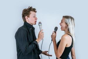 felice ritratto di coppia in possesso di microfoni e canto