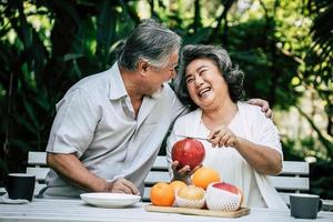 coppia di anziani affettare e mangiare frutta