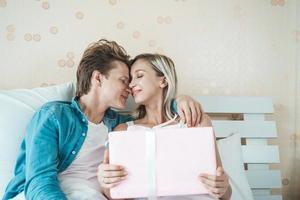 il ragazzo sorprende la sua ragazza con una confezione regalo sul letto