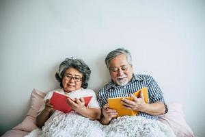 coppia di anziani sdraiata sul letto e leggere un libro