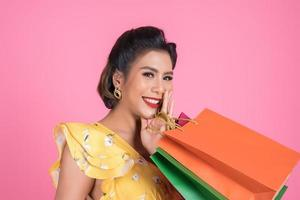 bella donna asiatica che tiene le borse della spesa colorate