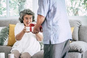 sorprese coppia di anziani con confezione regalo in soggiorno
