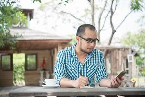 giovane imprenditore utilizza lo smartphone mentre si lavora nel giardino di casa