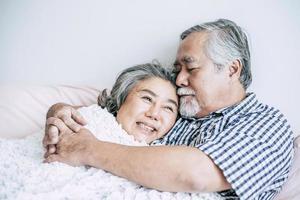 coppia senior sdraiata a letto insieme