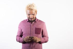 Ritratto di bello hipster barba uomo in piedi utilizza lo smartphone