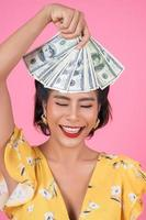 donna alla moda felice che tiene i soldi per lo shopping