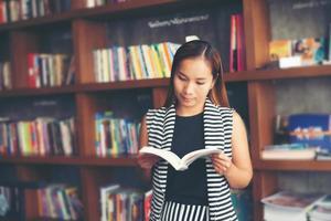 donna asiatica che legge un libro in biblioteca foto