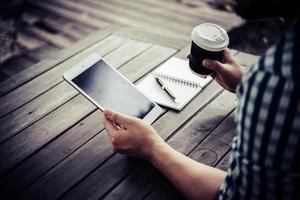 giovane uomo utilizzando la tavoletta digitale mentre beve il caffè seduto nel giardino di casa foto