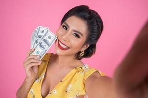 felice donna alla moda tenendo i soldi