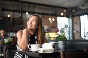 donna asiatica che si rilassa e che legge un libro nella caffetteria