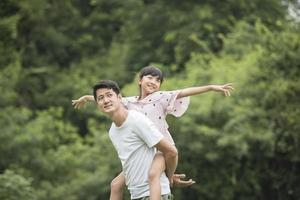 padre che trasporta la figlia sul retro nel parco foto