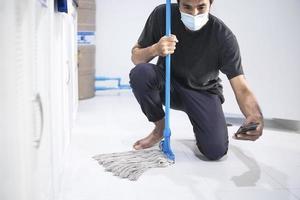 uomo asiatico che pulisce il pavimento foto