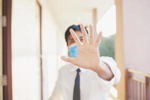 uomo asiatico tenendo la mano per mantenere la distanza foto