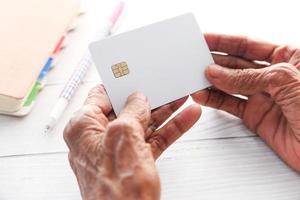 mano della donna senior che tiene una carta di credito foto