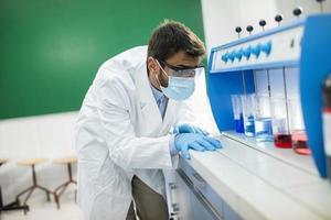giovane ricercatore con occhiali protettivi controllando le provette in flocculatore foto