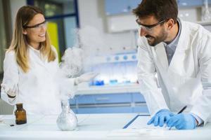 ricercatori che fanno esperimenti con il fumo su un tavolo di un laboratorio chimico foto