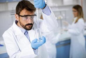 giovane ricercatore in indumenti da lavoro protettivi in piedi in laboratorio e analizzando il pallone con liquido foto