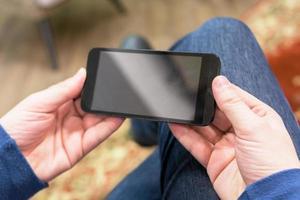 primo piano di un uomo che tiene uno smartphone mobile foto