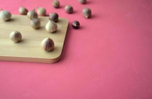 aglio sul tagliere su sfondo rosa foto