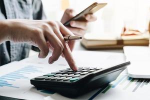 Close up di imprenditore utilizzando una calcolatrice foto