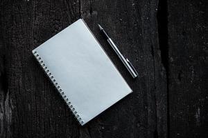 taccuino con la penna sulla priorità bassa di struttura di legno foto