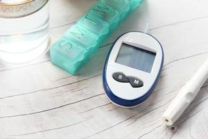 misuratore di glicemia, portapillole e bicchiere d'acqua sul tavolo foto