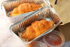 croissant in contenitori da asporto, da vicino foto