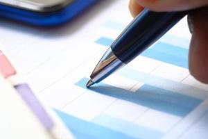 stretta di penna scrivendo su un grafico foto