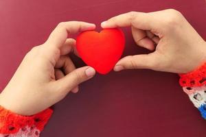 mani della donna che tengono un piccolo cuore rosso foto