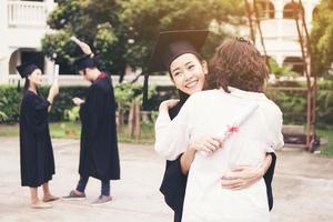 giovane laureato femminile che abbraccia sua madre alla cerimonia di laurea foto