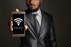 imprenditore mano che tiene il telefono con wifi vibrare i concetti del segno foto
