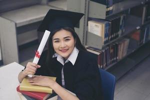 felice studente laureato in possesso di un diploma in mano foto
