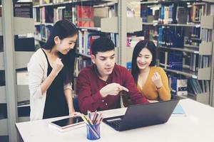 gruppo di studenti universitari che studiano nella biblioteca della scuola foto