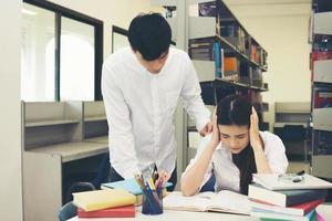 ritratto di studente che tocca la sua testa durante la lettura del libro nella biblioteca del college foto