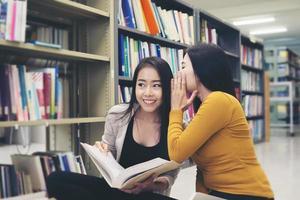 gruppo di studenti felici con libri a parlare e preparare per l'esame in biblioteca foto