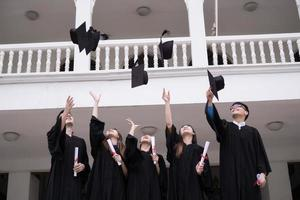 gruppo di studenti di successo che lanciano cappelli da laurea in aria e festeggiano foto