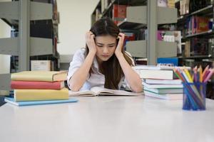 ritratto di studente toccando la testa durante la lettura del libro nella biblioteca del college foto
