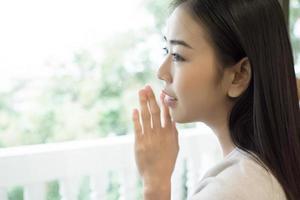 giovane bella donna in piedi vicino alla finestra a casa foto