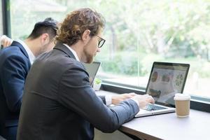 giovane uomo d'affari che lavora al computer portatile in ufficio foto