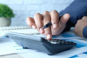 stretta di mano di un uomo utilizzando la calcolatrice foto