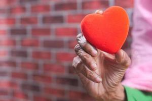 mano della donna senior che tiene cuore rosso da vicino foto