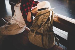 donna turistica giovane hipster con zaino seduto nella stazione ferroviaria foto