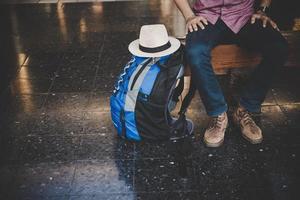 uomo giovane hipster seduto sulla panca in legno con zaino alla stazione ferroviaria foto