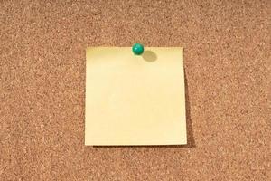 bacheca di sughero con nota gialla vuota per l'aggiunta di testo foto
