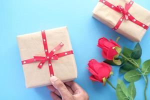mano d'uomo che tiene una confezione regalo su sfondo blu foto