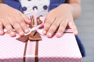 le mani del bambino su un regalo rosa foto